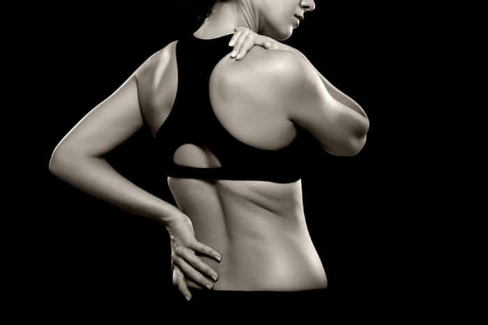 A black and white photo of an athletic woman holding her lower back and shoulder as if experiencing pain. Photographed in the studio. Isolated on a black background.
