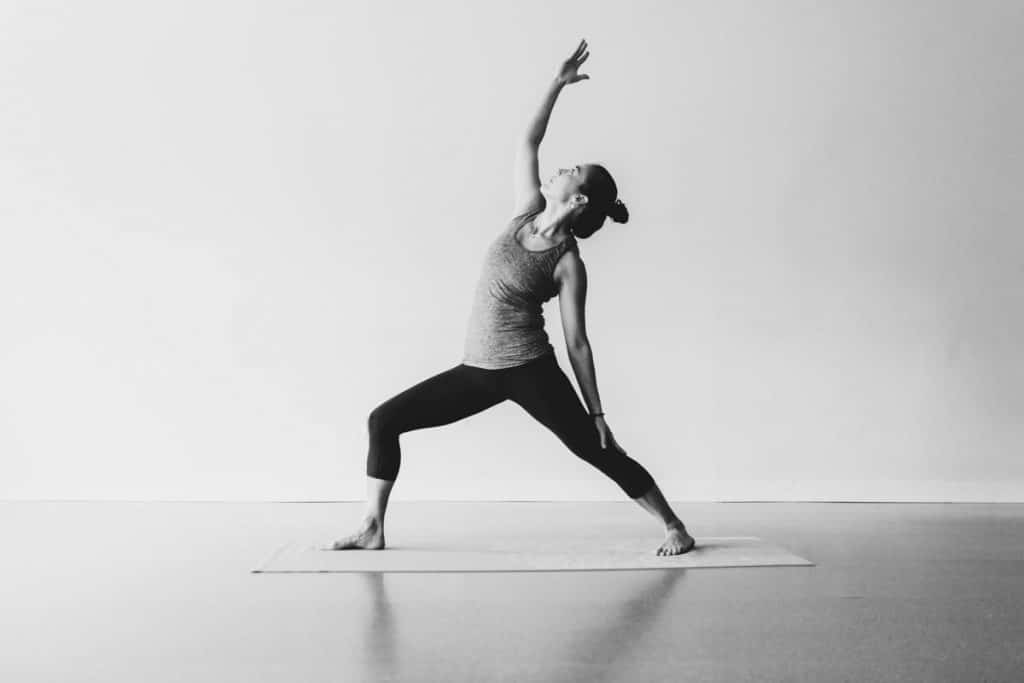 Lady showing a yoga pose in black and white